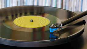 Turntable and record. A record spins on a turntable with a shelf full of albums in the background Stock Image
