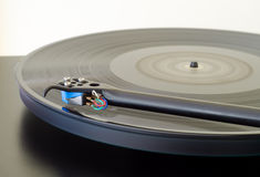 Turntable and Spinning Album. Black turntable, blue cartridge, spinning vinyl royalty free stock images