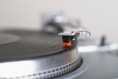Turntable tone-arm cartridge is playing disk. This stylish 20-years old turntable is playing disk. The tone-arm cartridge is in focus. You can put your logo and Royalty Free Stock Photo