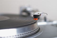 Turntable tone-arm cartridge is ready to play disk. This stylish 20-years old turntable is ready to play disk. The tone-arm cartridge is in focus. You can put Stock Image