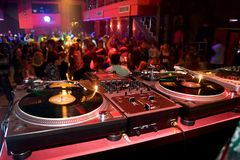 Turntables in the nightclub. Djs table with audio equipment in the crowded club Royalty Free Stock Photography