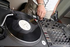 Turntables and spining record 2. DJ spining the record // 2 turntables and mixer Stock Photos