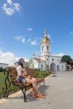 Turov, Bielorrússia - 7 de agosto de 2016: Catedral de Saint Cyril e da menina que descansa em um banco perto da igreja Turov do  Imagens de Stock