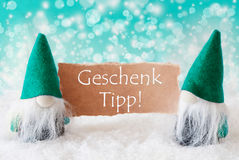 Turqoise Gnomes With Card, Geschenk Tipp Means Gift Tip Stock Photo