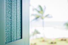 Turqoiuse ha dipinto l'otturatore della finestra che trascura l'oceano fotografia stock