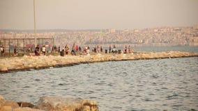 TURQUÍA - ESMIRNA KARSIYAKA - 20 de junio de 2015: Gente que sale y que cuelga en la playa bajo puesta del sol hermosa almacen de video
