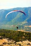 Turquia, Oludeniz - 23 de junho de 2015: O voo dos paragliders nas montanhas paragliding Tomando fotos de uma altura Fotografia de Stock Royalty Free