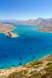 Turquise bevattnar av den Mirabello fjärden med den Spinalonga ön Royaltyfri Bild