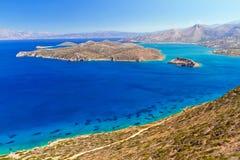 Turquise bevattnar av den Mirabello fjärden med den Spinalonga ön Royaltyfria Bilder