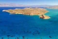 Turquise bevattnar av den Mirabello fjärden med den Spinalonga ön Arkivfoton