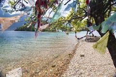 在Turquoise湖旁边的祷告旗子 免版税库存图片