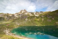 Turquoise alpine lake in mountains Stock Images