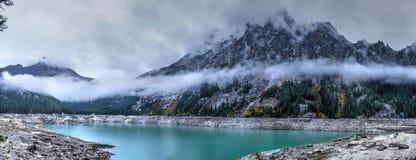 Turquoise alpiner See mit Bergen und Wolken Lizenzfreie Stockbilder