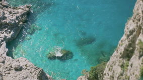 Turquoise Azure Blue Paradise Bay Capri Italy. Medium long high angle high dynamic range shallow depth of field shot looking down from a cliff on a beautiful bay stock video