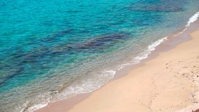 Turquoise azure sea waves breaking gently on a sandy beach. Turquoise crystal clear Aegean sea water waves breaking gently on a sandy beach coast line. Mykonos stock video