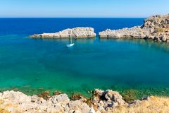 Turquoise bay in Lindos on Rhodes island in Greece. Azure crystal clear water in aegean sea in Rhodes island stock image