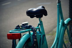 Turquoise Bike in Amsterdam, the Netherlands. Detail view of an old turquoise bike in the city of Amsterdam, in the Netherlands Stock Photo