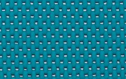 Blue perforated bath mat in a tub. A turquoise blue bath mat seen through a macro lens with perforations showing the porcelain bath tub underneath royalty free stock images