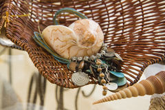 Turquoise blue ethnic  necklace and shells over straw basket Royalty Free Stock Images