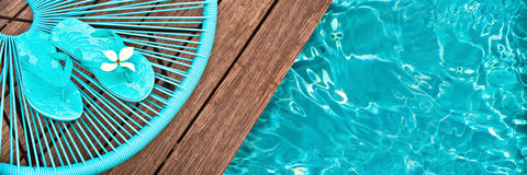 Turquoise blue garden chair and flip flops on on the edge of a swimming pool Royalty Free Stock Images