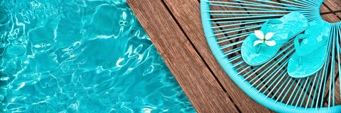 Turquoise blue garden chair and flip flops on the edge of a swimming pool Royalty Free Stock Photos