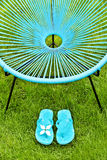 Turquoise blue garden chair and flip flops, green lawn Stock Photography