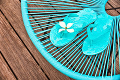 Turquoise blue garden chair and flip flops Royalty Free Stock Photography