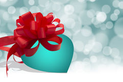 Turquoise blue heart with red bow on bokeh background Stock Photography