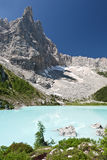 Turquoise Blue Mountain Lake. The milky turquoise waters of Lago de Lagazuoi rest lazily below the towering cliffs of the Dolomite Mountains in northern Italy royalty free stock images