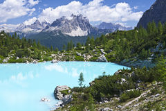 Turquoise Blue Mountain Lake. The milky turquoise waters of Lago de Sorapiss rest in the small valley below towering granite mountains in the Dolomites of stock image
