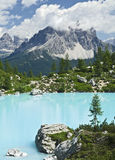 Turquoise Blue Mountain Lake. The milky turquoise waters of Lago de Sorapiss rest in the small valley below towering granite mountains in the Dolomites of Royalty Free Stock Photo