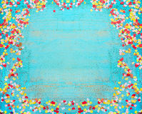Turquoise blue party background with confetti. Frame of confetti on shabby chic wooden background. Stock Photo