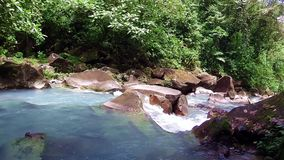 A turquoise blue river in Costa Rica. A river in Costa Rica. The color of the water is caused by the chemical reaction between calcium carbonate and sulfur stock video