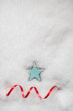 Turquoise Blue Star and Red Swirling Ribbon on Snow Royalty Free Stock Images