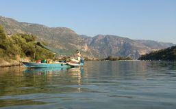 Turquoise boat. Bright boat with reflection in the sea with mountain on background in Fethie Turkey Royalty Free Stock Image