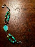 Turquoise bracelet on antique wood table top. Royalty Free Stock Photo