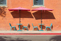 Turquoise Cafe Tables and Chairs with Pink Umbrellas. Outdoor cafe tables and chairs under windows in rust-colored brick wall Stock Image