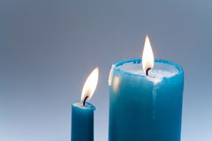 Turquoise candles with flames in motion. Macro view. soft focus. gradient gray background. Two pieces. Romantic still Royalty Free Stock Photography