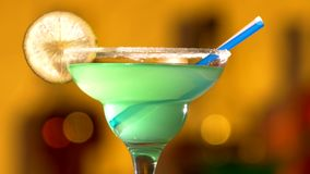 Turquoise cocktail with lime decortion and coconut. Turquoise delicious cocktail with lime decortion, tubules and coconut on edge, rotation, cam moves upwards stock video footage