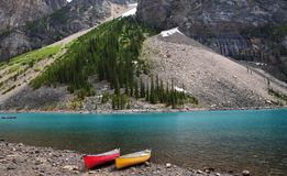 Turquoise color Moraine Lake with red and yellow canoe in Banff national park, located in Canadian Rockies in Alberta Canada stock image