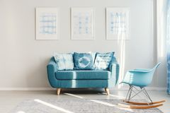 Turquoise couch in daily room. Blue rocking chair on grey carpet and turquoise couch with patterned pillows against white wall with gallery in daily room Royalty Free Stock Photo