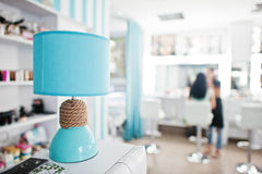 Turquoise desk lamp with decor cord on beauty studio. Royalty Free Stock Photos