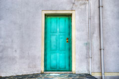 Turquoise door in a grey wall Royalty Free Stock Photography