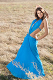 In turquoise dress. Beautiful woman wearing turquoise long dress standing in a meadow royalty free stock photos