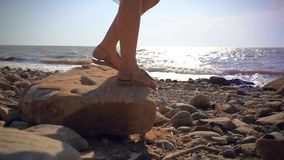 Turquoise dressed slim woman legs at the beach on. Stone and sunlight in sea. HD. 1920x1080 stock footage