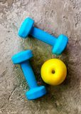 Turquoise dumbbells with measuring tape and yellow apple on concrete background. Free space for your text. Sport concept. Old dumbbells with measuring tape and Royalty Free Stock Photo