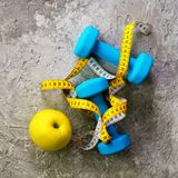 Turquoise dumbbells with measuring tape and yellow apple on concrete background. Free space for your text. Sport concept. Old dumbbells with measuring tape and Stock Images