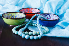 Turquoise earrings on bowl. Fashion background stock photo