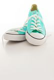 Turquoise et espadrilles blanches de toile sur un fond vide Image libre de droits