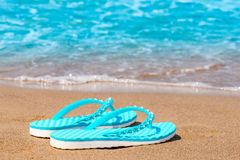 Turquoise flip flops abandoned on sandy seashore. Turquoise flip flops abandoned on a sandy seashore royalty free stock photography